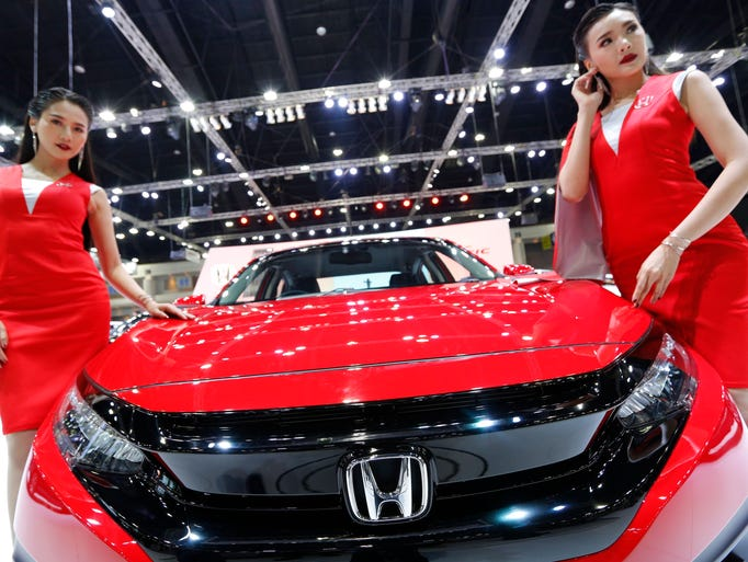 Models pose next to a Honda during the 34th Thailand