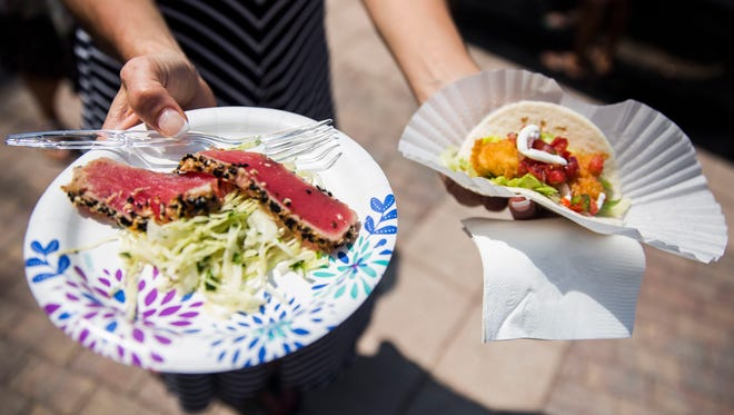 A woman walks away from the Chop 239 booth and the Mango Dockside Bistro booth with ahi tuna and fish tacos during the 27th Annual Taste of Marco at The Esplanade on Sunday, April 8, 2018.