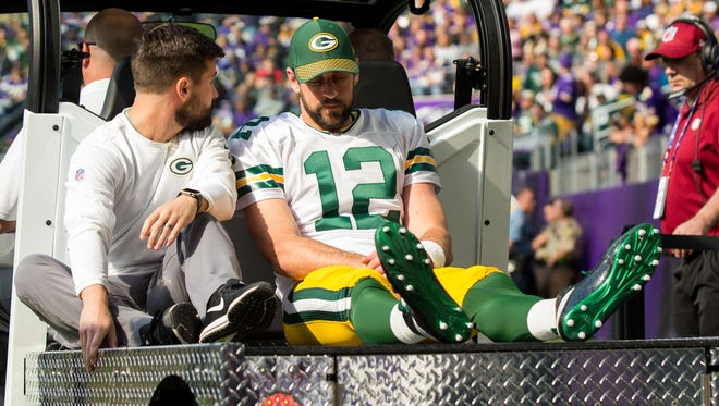 Green Bay Packers quarterback Aaron Rodgers (12) is taken off the field on a cart in the first quarter against the Minnesota Vikings at U.S. Bank Stadium.