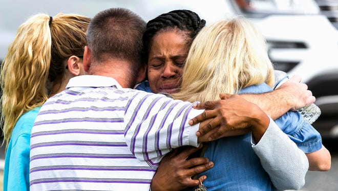 Nikki Brown, center, hugs others in front of Forest High School Friday, April 20, 2018 in Ocala, Fla. One student shot another in the ankle at the high school and a suspect is in custody, authorities said Friday.  The injured student was taken to a local hospital for treatment. (Doug Engle /Star-Banner via AP)