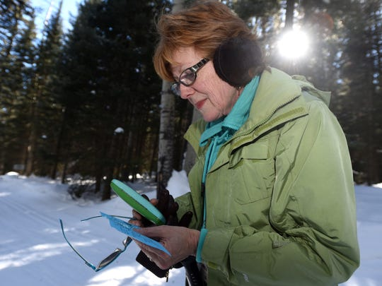 Sara Stover, of Flower Mound, Texas, consults her map while searching for a snowshoe trail on Friday at the Durango Nordic Center near Purgatory Resort in Colorado.
