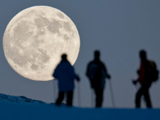 Three snow hikers watch the almost full moon rise behind