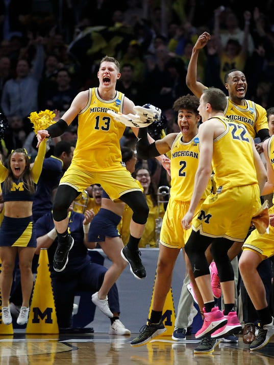 Michigan forward Moritz Wagner (13), guard Jordan Poole (2), guard Muhammad-Ali Abdur-Rahkman, top left, and guard Duncan Robinson (22) celebrate during the second half of the team's NCAA men's college basketball tournament regional semifinal against Texas A&M on Thursday, March 22, 2018, in Los Angeles. (AP Photo/Jae Hong)