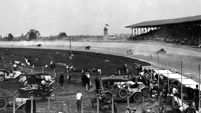 Roaring around the first turn at speeds of 75 mph, four racers duel for position in the first running of the Indianaolis 500 on May 30, 1911.  The cloth covered pits in the lower right hand side keep the hot Indiana sun from the mechanics.