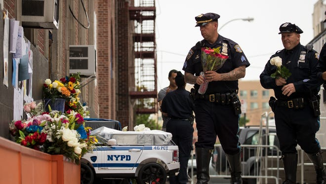 Members of the New York City Police Department arrive with flowers at a makeshift memorial for fallen NYPD officer Miosotis Familia outside the 46th Police Precinct in the Bronx borough of New York City. NYPD officer Miosotis Familia, 48, was shot and killed as she sat in a command vehicle in the Bronx in what police are calling an unprovoked attack.