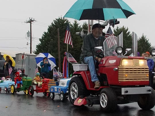 A lawnmower pulls pedal toys with stuffed animal riders Sunday through the Denver Downs Christmas Parade.