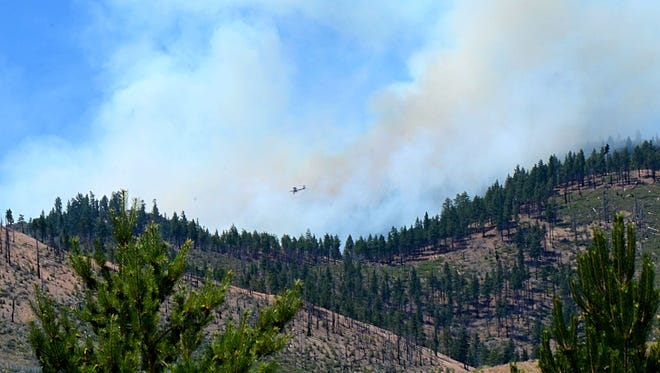A single engine airtanker is seen flying overhead of the Evans Fire, which sparked early Sunday morning and burned 60 acres at Evans Canyon area in southwest Reno.