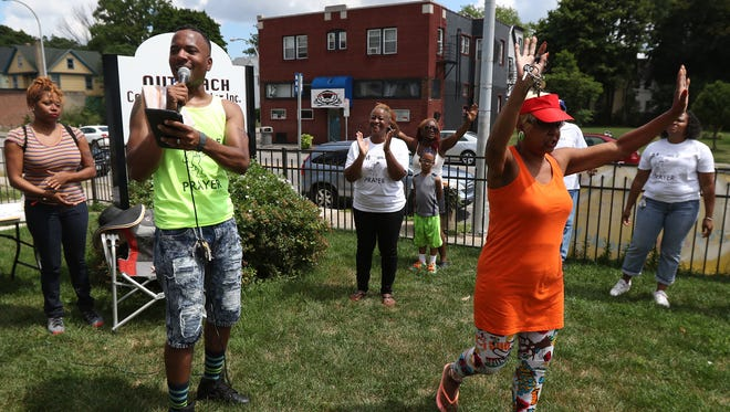 Pastor Kelvin Dailey of Faith, Healing and Deliverance Clinic held a mobile prayer clinic on the front lawn of the Outreach Community Center on the corner of Genesee and Aldine streets.   Lincie Anderson raises her hands in praise of God.
