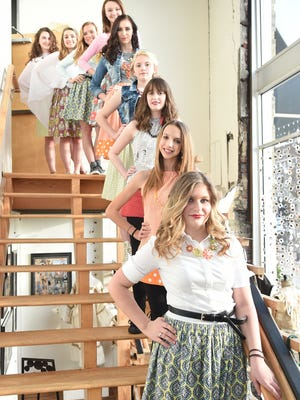 Savannah Johnson, 14, bottom right, poses for a portrait with models showing off her debut designs during Knoxville Fashion Week at The Emporium Center during last year's Knoxville Fashion Week.