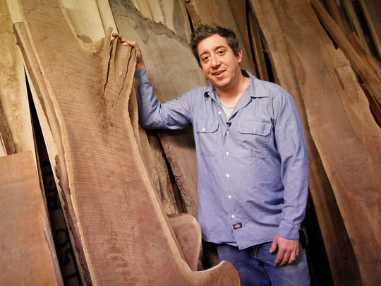 Indianapolis artist Brian Presnell is shown with some wood from downed or damaged trees that he is planning to mill to turn them into new art and furniture.