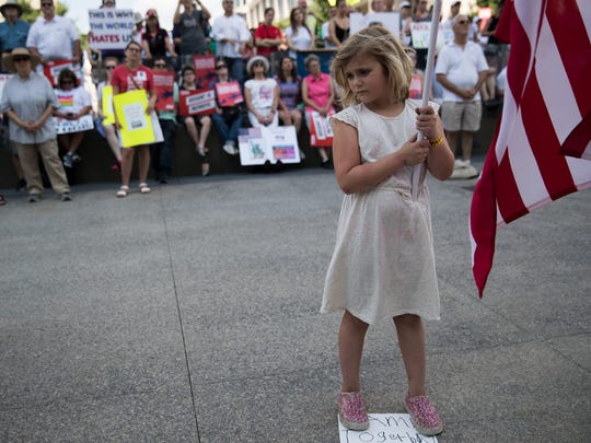 Josephine Shaver, 8, Indianapolis, holds an American flag as she attends an immigration protest at the Indiana Statehouse organized by the ACLU, on June 30, 2018.