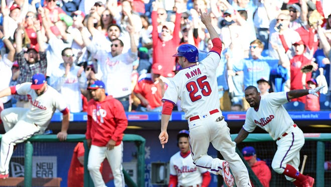 The Philadelphia Phillies'  Daniel Nava celebrates after scoring the game-winning run in the bottom of the ninth inning against the Washington Nationals.