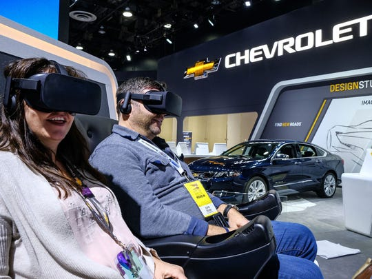 Myki Bowling, a General Motors employee and John Rehm of Jack Morton take part in a virtual simulation of being the passenger in car testing at Milford Proving Ground in the Chevrolet section as the area is prepped for the upcoming North American International Auto Show at Cobo Center in downtown Detroit on Friday, January12, 2018.