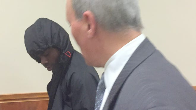 Davarcea Fort, with hood, exits court with his attorney Don Scalia.