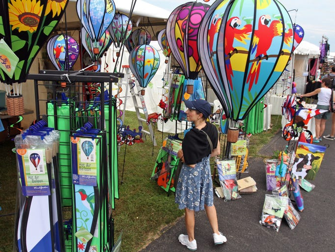 It is not just hot air balloons at the Quick Check New Jersey Festival of Ballooning at Solberg Airport. Catherine Grad of Newburgh New York looks over decorative wind powered balloons at one of the vendor tents. Grad said that she and her husband Mark opted for the festival instead of the beach since it was overcast this morning, July 26 2014. Whitehouse Station NJ. Photo by Kathy Johnson BRI EST 0727 Balloon festival
