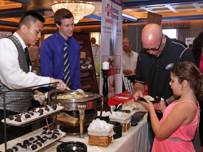 The Somerset County Business Partnership holds its annual Biz Fest, an expo for county businesses, held at the Imperia.  Lafonso Adoptante, left, and Andrew Manganelli, both of Maggiano's, serve Gary Perlinsky and his daughter Alexia,9, during the event, June 19, 2014. Franklin NJ. photo by Kathy Johnson  BRI 0621 Biz Fest Standalone