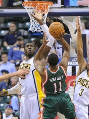Brandon Knight of the Bucks has a tough shot over Roy Hibbert and George Hill of the Pacers. The Indiana Pacers hosted the Milwaukee Bucks in NBA action at Bankers Life Fieldhouse Thursday February 27, 2014.