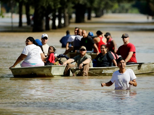 People evacuate a neighborhood inundated after water was released from nearby Addicks Reservoir when it reached capacity due to Tropical Storm Harvey on Wednesday, Aug. 30, 2017, in Houston. (AP Photo/Charlie Riedel)