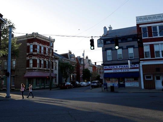 Two women cross a street in Covington, Ky., on April