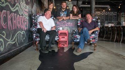 Partners Bob Conway and Mark Schultz sit in the entry of Newport's Packhouse Meats with servers Kimber Schultz, Matthew Johnson and Suz Schultz. The restaurant opened in January with a no tipping policy.