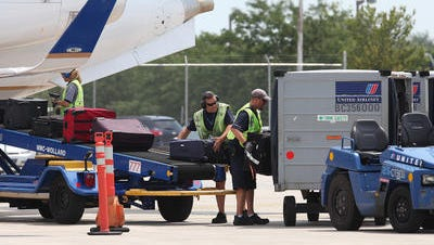 United Airlines workers load bags at the Des Moines International Airport.