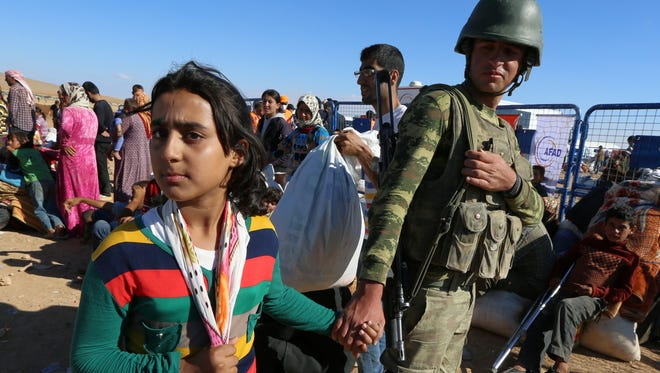 A Turkish soldier holds the hand of Sidra, 12, a Kurdish refugee girl from Kobani who lost her parents after their arrival at the Turkey-Syria border near Suruc, Turkey, Tuesday, Sept. 30, 2014.