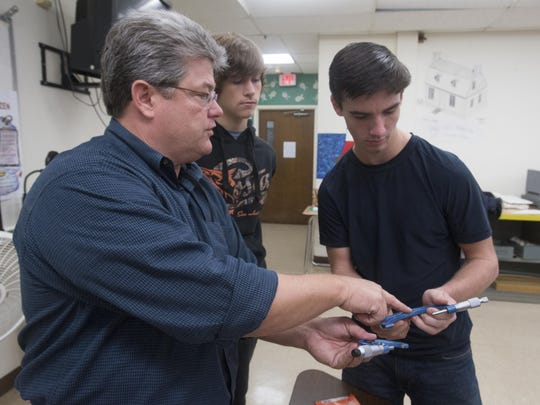 Washington High School teacher, Kyle Cook, left, teaches students, Christian Shiver, center, and Nicholas Stinson, right, how to take precision measurements using precision tools during aviation maintenance class Monday morning Nov. 9, 2015.