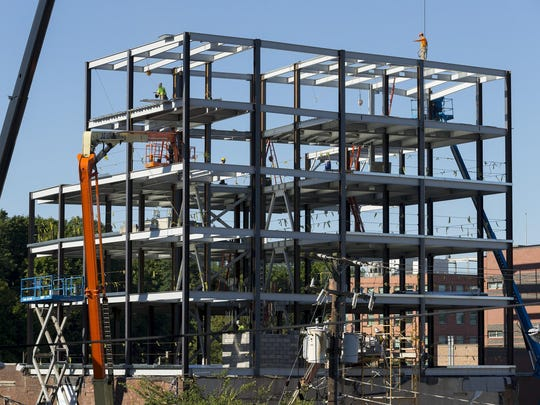 Construction workers add steel Thursday morning to the Carey Building on E. State Street that is Rev's permanent location. Travis-Hyde Properties, is enlarging the building from two stories to seven.