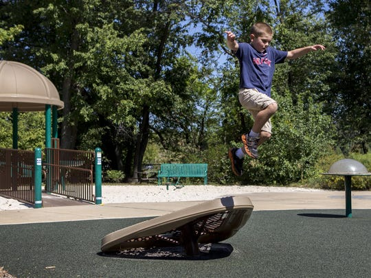 Five year-old Gus Partridge leaps off a piece of playground equipment in the Can-Do Playground at Alapocas Run State Park on Thursday afternoon.