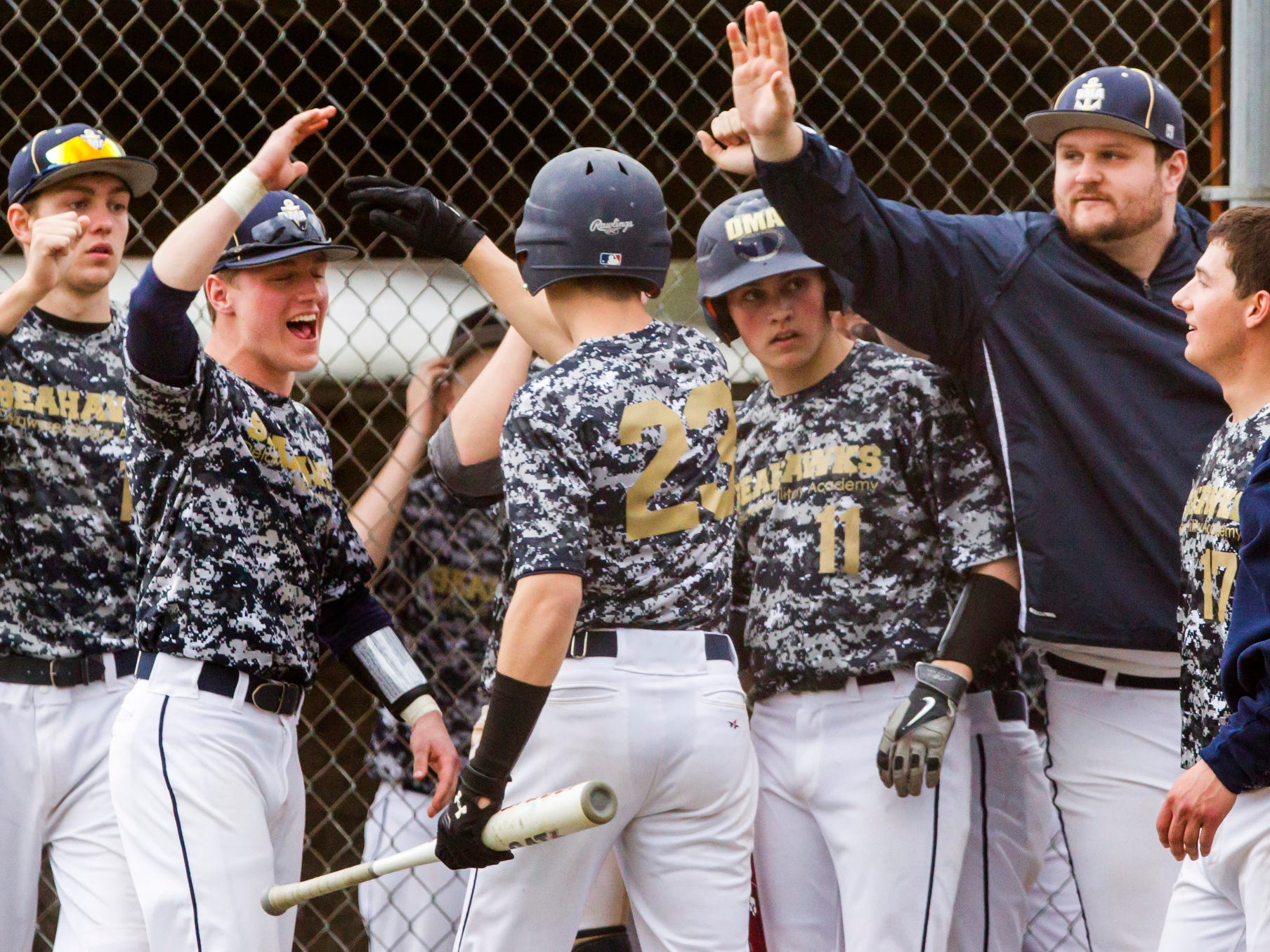 Delaware Military Academy players congratulate Shane Carney after he scored the tying run during a game at Newark National field on Tuesday afternoon.