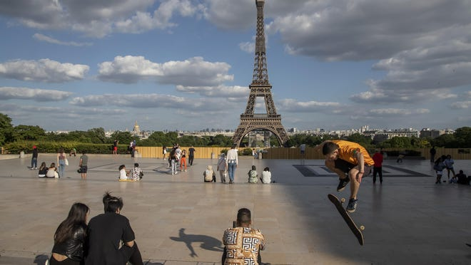 In this Monday, May 25, 2020 file photo, people stroll at Trocadero square near the Eiffel Tower in Paris. European Union envoys are close to finalizing a list of countries whose citizens will be allowed back into Europe once it begins lifting coronavirus-linked restrictions. The United States appears almost certain not to make the list, as new infections surge and given that President Donald Trump has imposed a ban on European travelers.