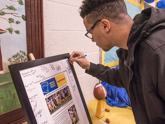 Senior Blake Hartsfield signs a framed news feature about the team.