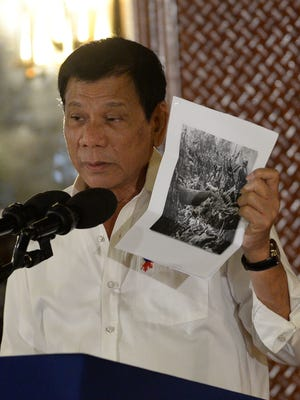 Philippine President Rodrigo Duterte holds up a photo -- and cites accounts of U.S. troops who killed Muslims during the U.S. occupation of the Philippines in the early-1900 -- during a speech in Manila on Sept. 12, 2016.