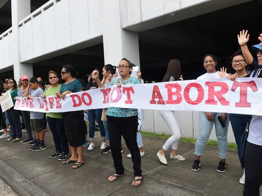 """Chain for Life"" protest participants display a large anti-abortion banner at the Guam International Trade Center intersection in Tamuning on Jan. 22, 2017."