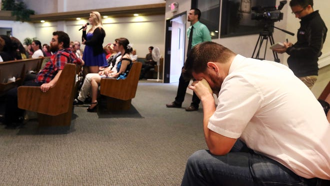 Former Roseburg High School math teacher Josh Carlton wipes away tears as Taylor Moore recounts a memory from her time as classmate of Quinn Cooper during a memorial for Cooper at Roseburg Christian Fellowship church in Roseburg, Ore., on Saturday, Oct. 10, 2015. Cooper was killed when a gunman opened fire at Umpqua Community College before turning the gun on himself after a shootout with police. (Michael Sullivan/The News-Review via AP)