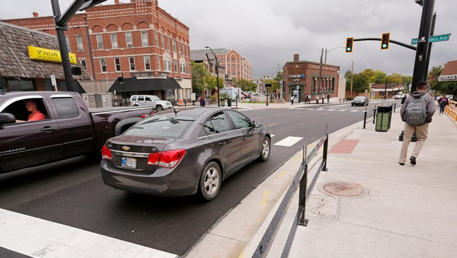Traffic passes through the intersection of State Street and Northwestern Avenue in the Chauncey Village Wednesday, September 13, 2017, in West Lafayette. John von Erdmannsdorff, owner of Von's Shops, circulated a petition to stop the planned closure of State Street and Northwestern Avenue on home Purdue football game days. The petition contains over 40 signatures of managers and owners of businesses in the Chauncey Village who are against the closure, which the city will test out on the Sept. 23 Homecoming game.