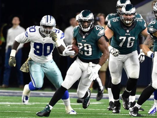 DeMarco Murray (29) finds running room with help from offensive guard Allen Barbre (76) as Cowboys' Demarcus Lawrence (90) gives chase Sunday.