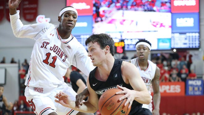 Binghamton guard Timmy Rose drives past St. John's Red Storm forward Tariq Owens during the first half at Carnesecca Arena in New York.