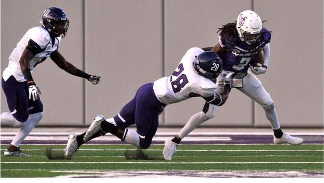 Abilene Christian University wide receiver DeShun Qualls is tackled by Stephen F. Austin University safety Marlon Walls during Saturday's game at Wildcat Stadium Sept. 23, 2017. ACU lost, 10-20.