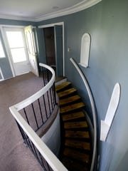 The curved staircase welcomes visitors as they walk through the front door at a foreclosed home on Michigan Road May 27 in Dimondale. The home will be auctioned off by the county in September.