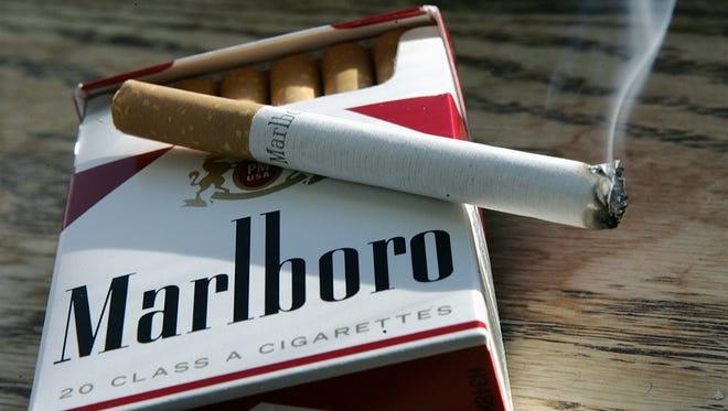 A Marlboro cigarette burns as it sits on a pack of Marlboro cigarettes.