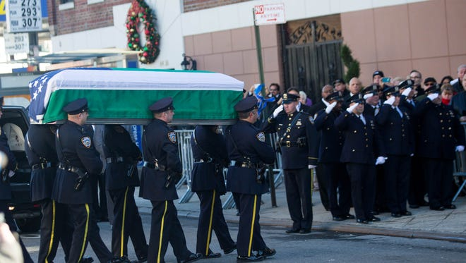 The casket of New York City police officer Rafael Ramos is carried into Christ Tabernacle Church prior to his wake  in the Glendale neighborhood of Queens in New York City, Dec. 26, 2014.