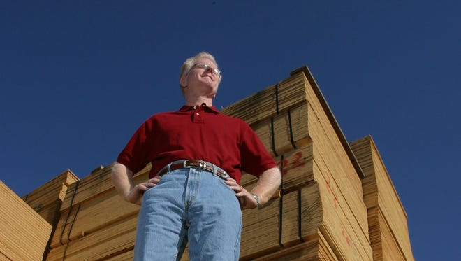 Frank Heldt of Heldt Lumber Co. stands on a stack of plywood at his store in 2004.