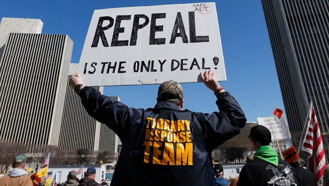A gun rights activist holds a sign during a rally at the Empire State Plaza on Tuesday, April 1, in Albany. Activists are seeking a repeal of a 2013 state law that outlawed the sales of some popular guns like the AR-15. The law championed by New York Gov. Andrew Cuomo has been criticized as unconstitutional by some gun rights activists.