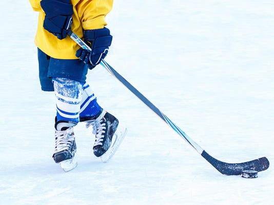 Legs of the hockey player, stick and washer close-up.