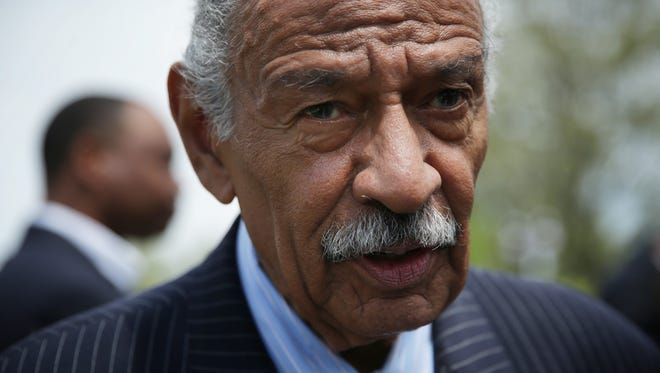 Rep. John Conyers speaks to a reporter at the end of a news conference April 22, 2015 on Capitol Hill in Washington, DC.
