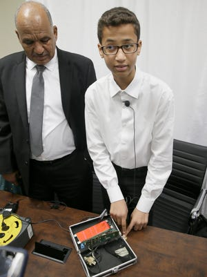 Ahmed Mohamed, right, shows the clock he built in a school pencil box while standing with his father Mohamed Elhassan Mohamed after a news conference in Dallas, Monday, Aug. 8, 2016.  The family of Ahmed Mohamed, who was arrested after bringing the homemade clock to school and charged with having a hoax bomb, filed a federal lawsuit Monday against Texas school officials and others, saying they violated the 14-year-old boy's civil rights.