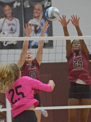 Salina Central's Tyler Vidricksen (10) and Mykayla Cunningham (24) try to block the hit from Salina South's Lauren Harris (25) during a match at the Central gym in 2020.