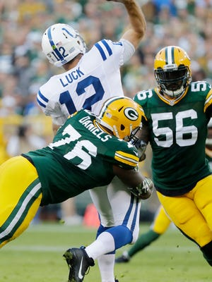 Green Bay Packers defensive end Mike Daniels (76) hits Indianapolis Colts quarterback Andrew Luck (12) as he throws