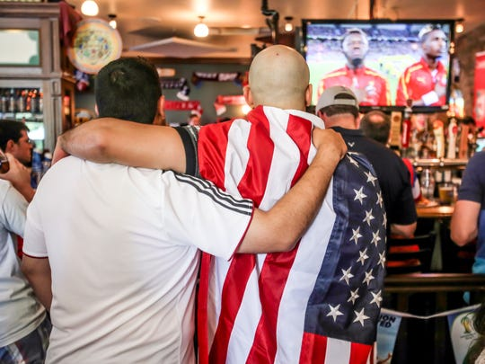 Monday June 16th, 2014, Addalla Abdalla (left), and Anisse Adni (right) stand for the national anthems, while watching the U.S.A. V.S. Ghana, in The World Cup, at Chatham Tap in Fishers Indiana.